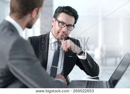 two businessmen discussing information from a laptop.