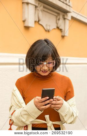 Indian Woman Texting In An Urban Context
