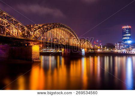 View Of The Hohenzollern Bridge, The Illuminated Skyscraper Cologne Triangle And The Long River Rhin
