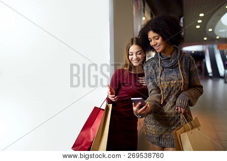 Two Happy Multiethnic Young Mixed Race Woman Shopping For Lingerie Near White Shop Window Copyspace,