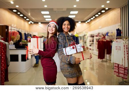 Two Mixed Race Women With Gift Boxes In Hands At Store. Multi Ethnic Girls Smiling With Presents On