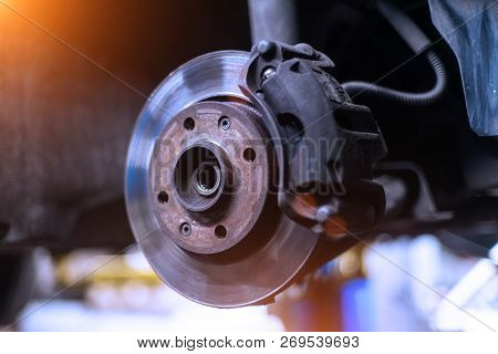 Car brake disk and caliper close up without wheel in cold colors with beautiful backlight poster