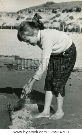 Vintage unretouched photo of young girl playing with sand