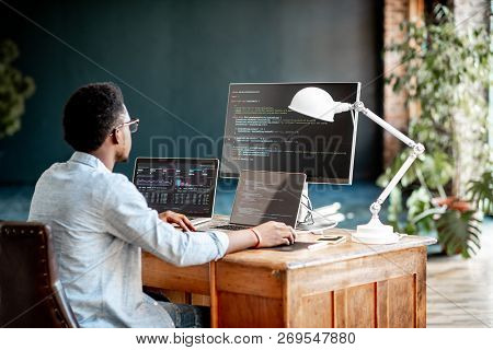 Young African Male Programmer Writing Program Code Sitting At The Workplace With Three Monitors In T