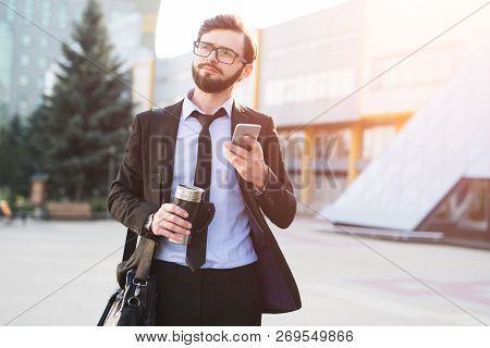 Hipster Impressed Businessman Using Smartphone On Office Build Background With Coffee Thermo Mug In