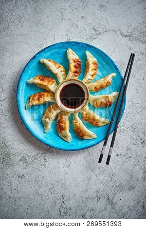 Traditional asian dumplings Gyozas on turqoise ceramic hand painted plate served with chopsticks and bowl of soy sauce over concrete texture background. Top view with copy space.