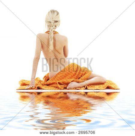 Senhora bonita com toalhas de laranja na areia branca