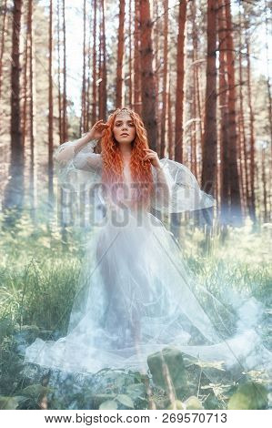 Beautiful Redhead Woman Forest Nymph In A Blue Transparent Light Dress In The Woods Spinning In Danc