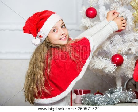 Family tradition concept. Child decorating christmas tree with red balls ornaments. Girl kid decorating christmas tree. Cherished holiday activity. Kid in santa hat decorating christmas tree poster
