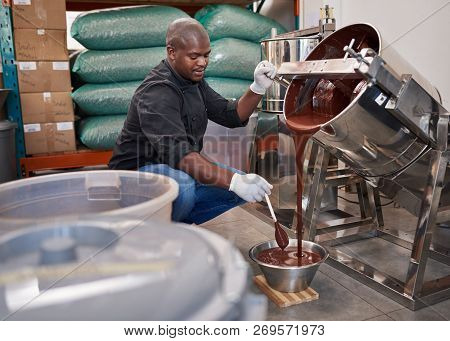 Worker Melting Chocolate While Working In A Confectionary Factory
