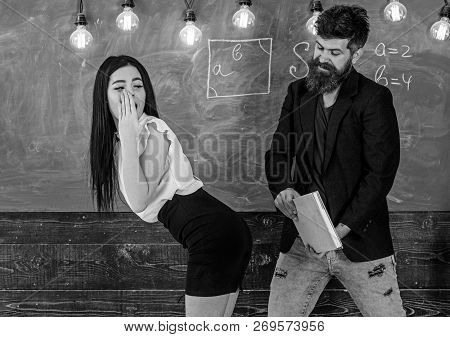 Man with beard slapping sexy student, chalkboard on background. Girl on guilty and helpless face punished by teacher. Schoolmaster punishes sexy student with slapping on her buttocks. Sex game concep poster