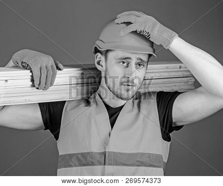 Carpenter, Woodworker, Strong Builder On Serious Face Carries Wooden Beam On Shoulder. Safety And Pr