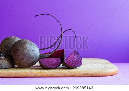Ripe Beetroot And Sliced Beet Vegetables On Cutting Board, Purple Background.