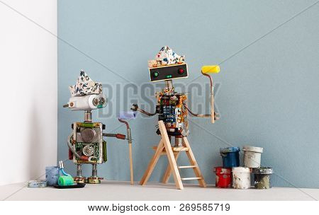 Two Robots Painters With Paint Rollers, Wooden Ladder And Paint Buckets Ready For Apartment Improvem