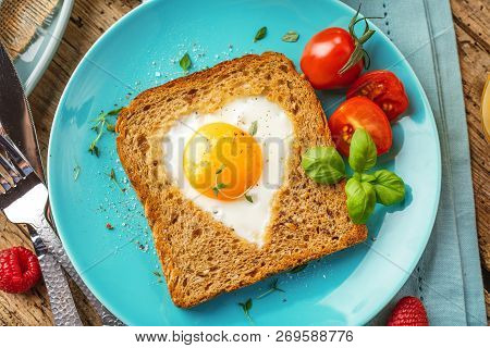 Breakfast On Valentine's Day - Fried Eggs And Bread In The Shape Of A Heart And Fresh Vegetables