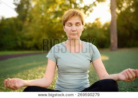 Mature Woman Practicing Yoga Outdoor Exercise Or Meditating. Healthy Lifestyle.