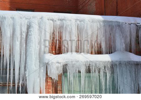 Long, Big And Dangerous Icicles On A Brick House Roof