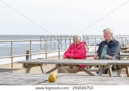 Southwold, Uk - September 8, 18 - Senior Couple Sitting On The Seaside Table Bench Looking Over The