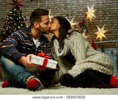 Christmas couple at home in Winter. Happy young couple sitting on floor at home with gift box in Christmas time. Christmas tree and fireplace in background.