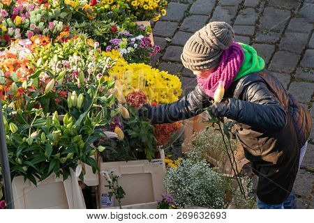 Prague, Czech Republic - November 17, 2018: Woman Buys Flowers At The Popular Farmers Market At The