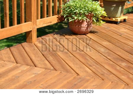 a pine colored deck with some plants poster