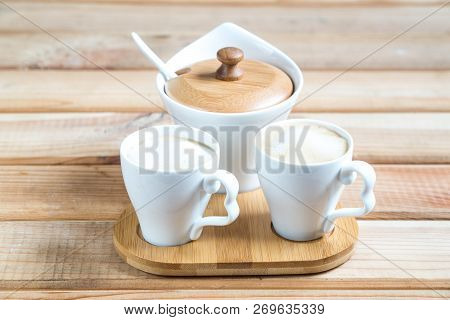 Coffee Creamers. Two Cups Of Coffee On A Wooden Table.