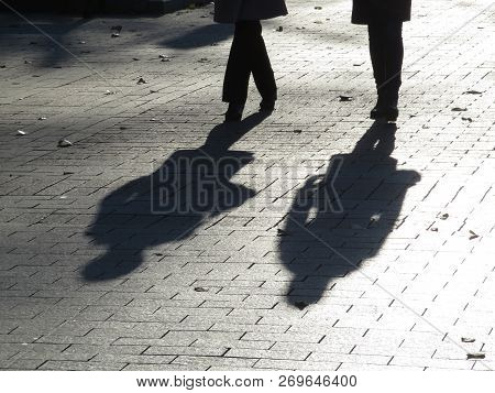 Silhouettes And Shadows Of Two People Walking Down The Street. Women Outdoors, Pedestrians On Sidewa