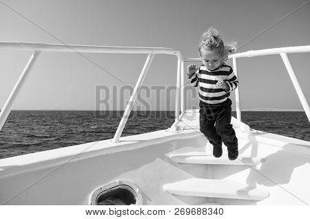 Freedom And Joy. Adventure Boy Sailor Travelling Sea. Child Cute Sailor Carefree Jump Yacht Bow. Boy