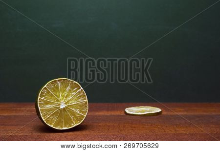 Cross Section Of A Lime And A Lime Slice On A Wooden Table. Green Background. Organic Accent To The Flavors Of Foods And Beverages. poster