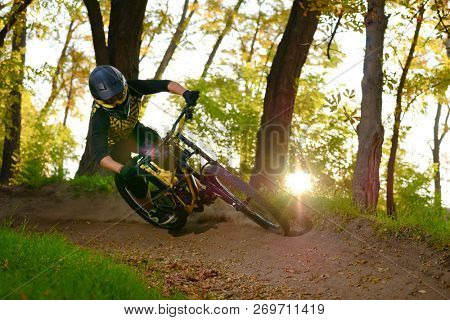 Professional DH Cyclist Riding the Mountain Bike on the Autumn Forest Trail at Sunset. Extreme Sport and Enduro Cycling Concept.