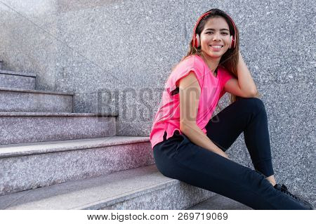 Portrait Of Happy Teenage Girl Sitting On Stairs In Headphones. Young Latin American Woman Listening