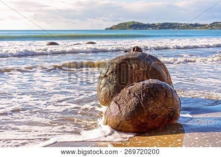 Two large spherical Moeraki boulders exposed in the beach surf on the Otago coast of New Zealand poster