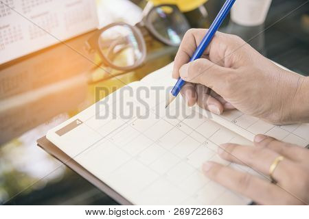 Close Up Of Female Hand Planner Or Organizer Writing Appointment On 2017 Calendar Page.woman Mark An