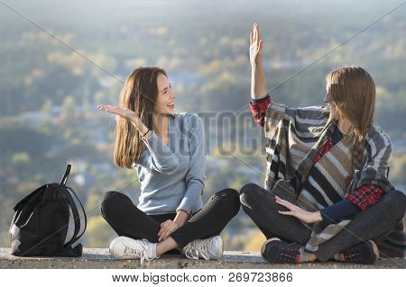 Two Smiling Women High Five Sitting On A Hill. Sunny Day