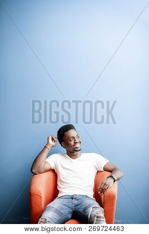 Portrait Of A Young African Man Dressed In White T-shirt And Jeans Sitting On The Chair On The Color