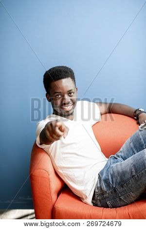 Emotional Portrait Of A Young African Man Dressed In White T-shirt And Jeans Sitting On The Chair On
