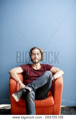 Portrait Of A Young Caucasian Bearded Man With Long Hair Dressed In T-shirt And Jeans Sitting On The