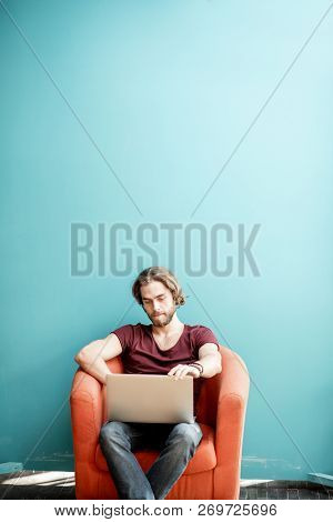 Portrait Of A Young Caucasian Bearded Man With Long Hair Dressed In T-shirt Working With Laptop On T