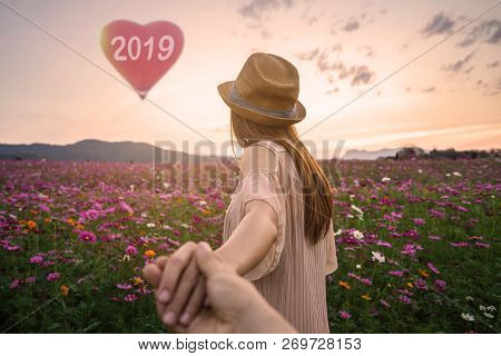 Young Woman Traveler Holding Man's Hand And Leading Him, New Year 2019 Celebration Concept