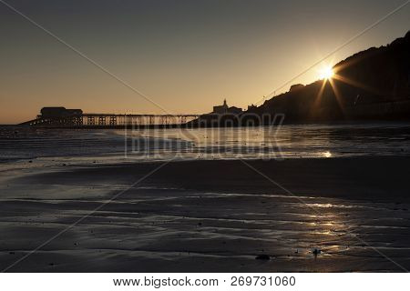 Starburst Sunrise At A Silhouetted Mumbles Pier And Lighthouse In Swansea, South Wales, Uk