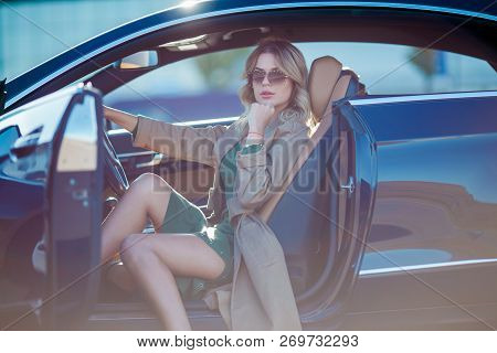 Photo Of Young Blonde With Glasses And Long Dress Sitting In Car With Open Door In Afternoon.lensfla