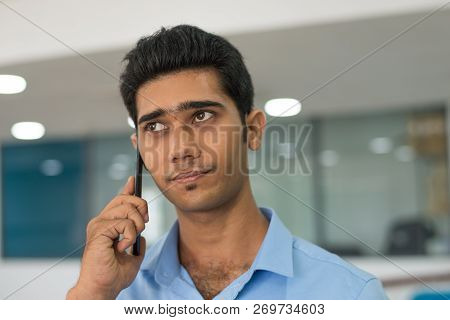 Pensive Handsome Man Listening To Customer On Mobile Phone. Concentrated Businessman Talking On Phon