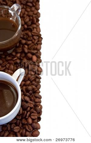 Coffee cups lying on a bed of coffee beans, isolated on white
