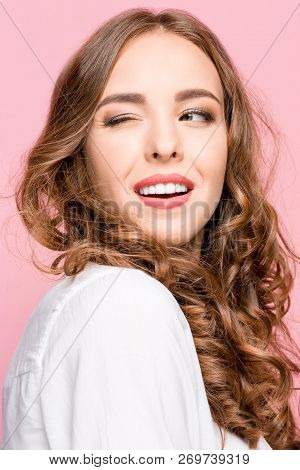 Happy Winking Business Woman Standing And Smiling Isolated On Pink Studio Background. Beautiful Fema