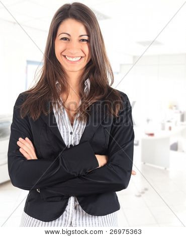 Portrait of a cute young business woman smiling, in an office environment