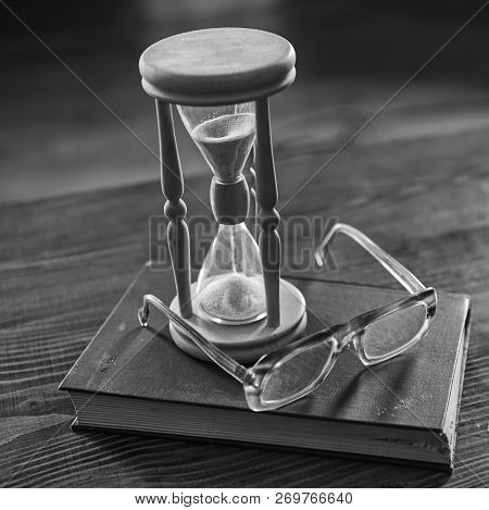 Time Flow Concept. Hourglass, Old Book And Eyeglasses On Wooden Table, Wooden Background.wooden Hour