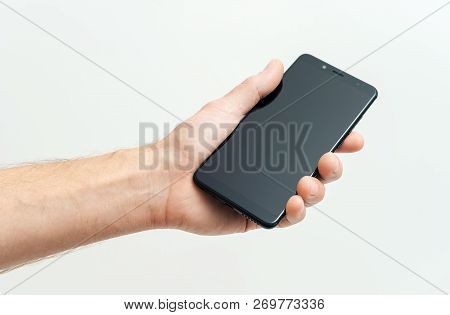 The Human Hand Is Holding A Black Smartphone On A White Background.