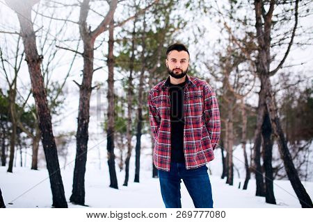 Portrait Of Handsome Bearded Young Man In Red Plaid Shirt Standing In Winter Snowy Forest. Stylish M