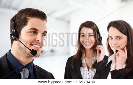 Portrait of a friendly phone operator. Two female operators in the bright and blurred background.