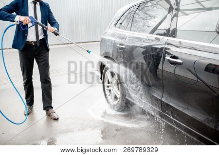 Businessman Dressed In The Suit Washing His Luxury Car With Washing Gun On A Self Service Open Air C